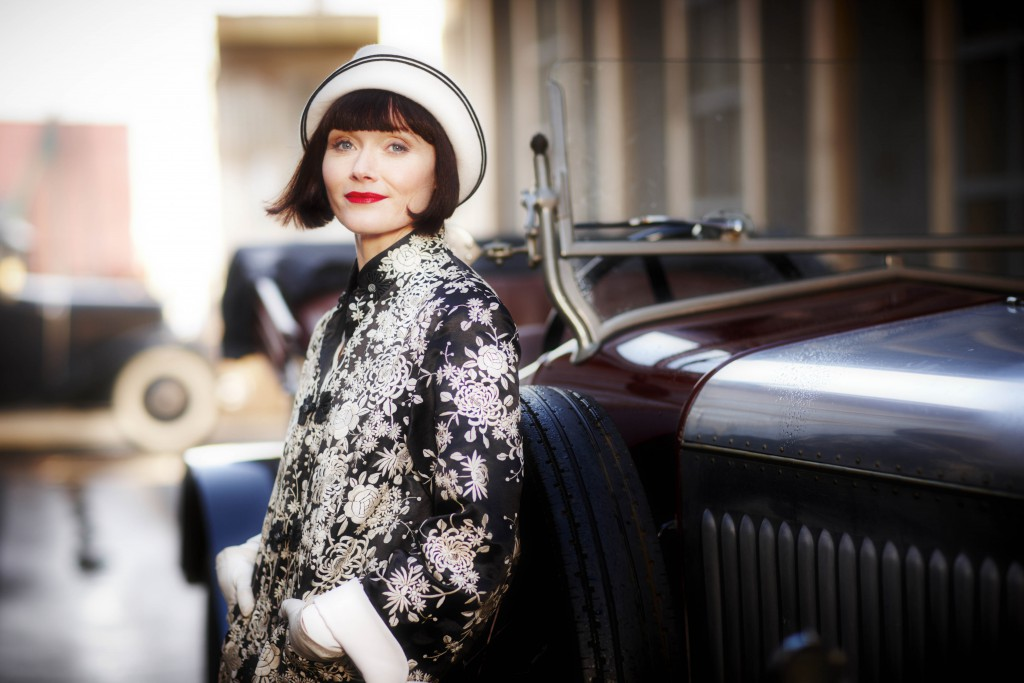 Miss Fisher leaning against her car.